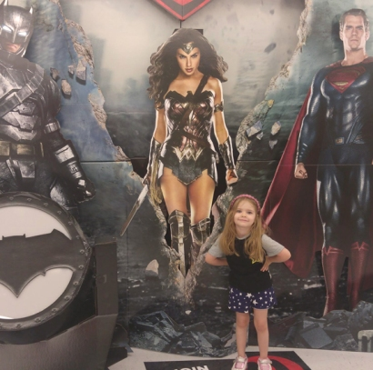 My granddaughter with movie poster in her super hero pose