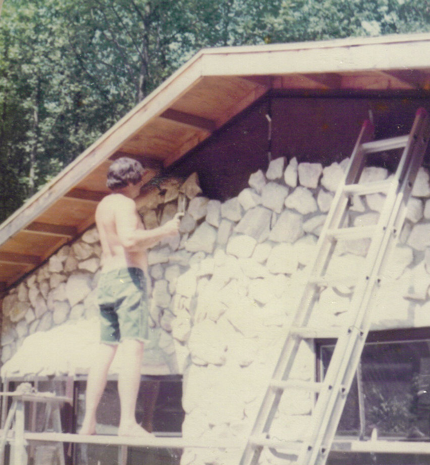 Dad laying stone on house