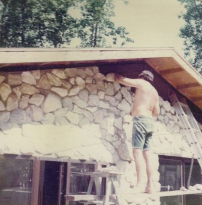 Dad laying the white Georgia marble stone on back of the house