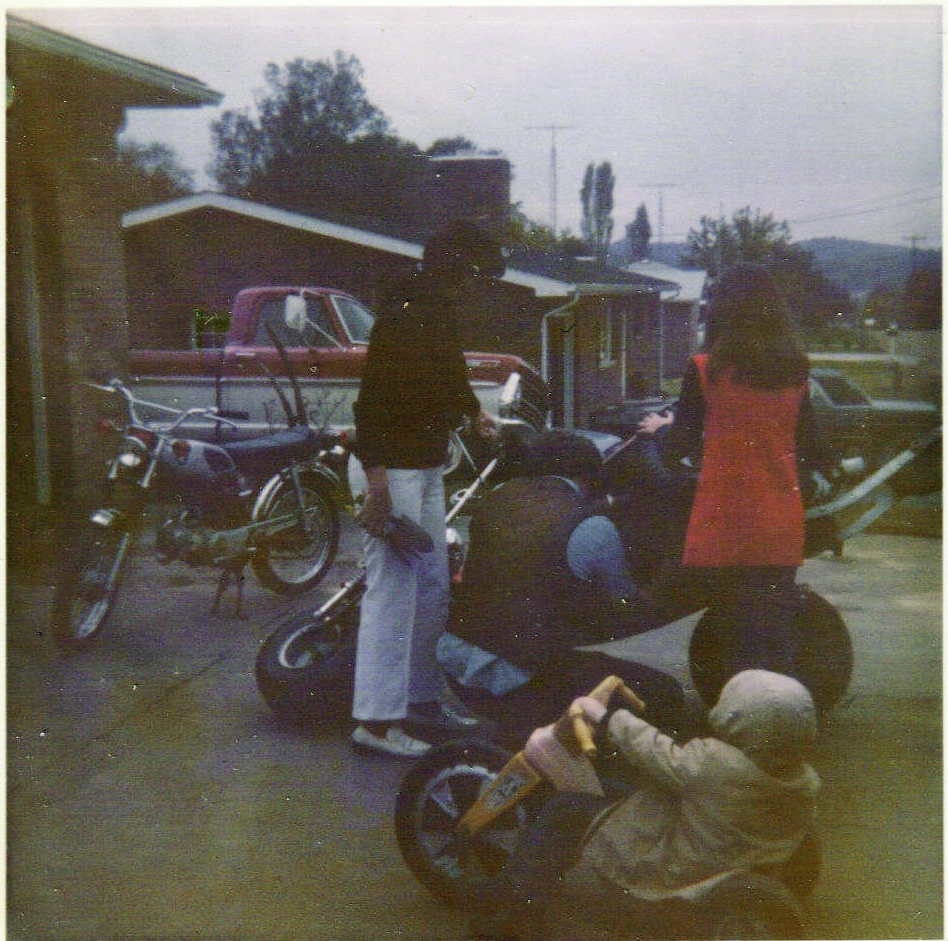 Dad working on a trike mom and Sheila watching with Greg on hot wheels